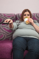 Woman with overweight eating a burger and watching tv