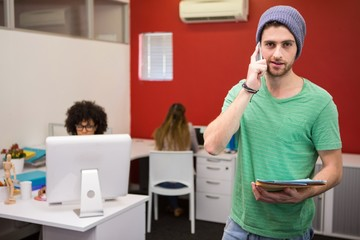 Casual businessman using cellphone in office