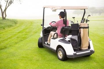 Golfer driving in his golf buggy
