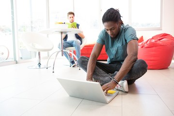 Casual young man using laptop on floor