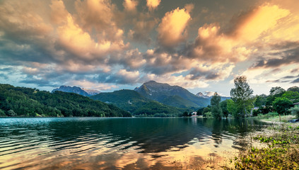 vibrant intense sunset landscape on lake and mountain background © darkside17