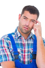 Portrait of confused manual worker scratching head