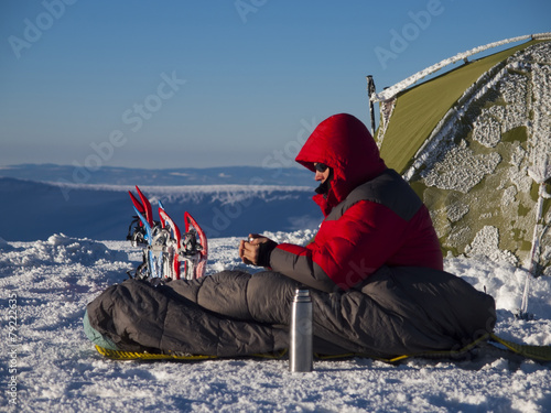 Foto op Canvas Alpinisme A man sits in a sleeping bag near the tent and snowshoes.