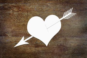 Heart pierced by an arrow on wooden background