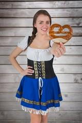 Composite image of pretty oktoberfest girl holding pretzel