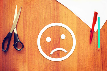 Sad emoticon made of paper on the desk. Concept of melancholy