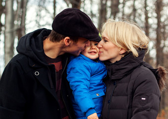 Loving parents kissing their son in the nature