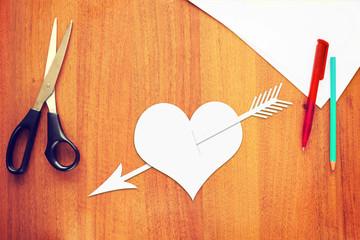 Symbol of love a paper heart pierced by an arrow