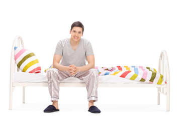 Cheerful young guy sitting on a bed