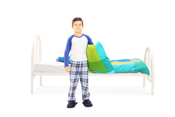 Little boy with pillow standing in front of a bed