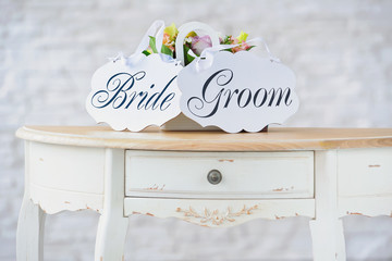 Bride and groom decoration boards with flowers on vintage table