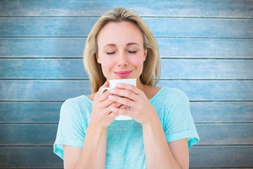 Composite image of cheerful blonde holding mug of hot drinking