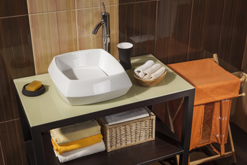 detail of a modern bathroom with sink, towels and laundry basket