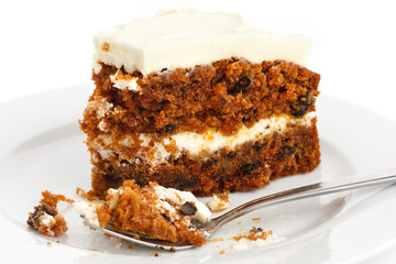 Slice of carrot cake with rich frosting. On plate.