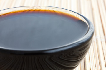Soja sauce in small glass dish. On bamboo mat.