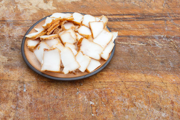 Pieces of smoked lard on ceramic plate. Place for text.