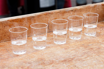 Row of shot glasses with vodka on wooden board.