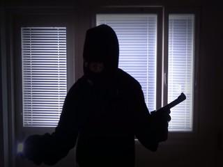 Burglar with gun breaking in from window