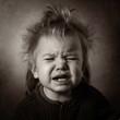 monochrome portrait of a sobbing baby on a dark background