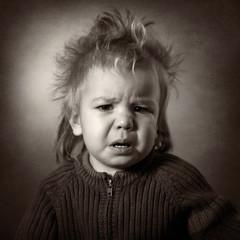 monochrome portrait of upset baby on a dark background