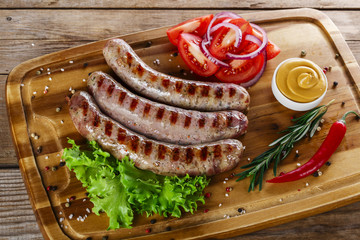 grilled sausages on the grill on the board