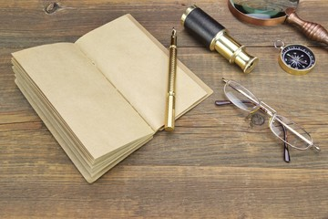 Notebook, Pen, Glasses, Magnifier, Cpmpass and Spyglass On Wood