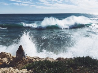 girl sitting on the edge of rock watching the waves