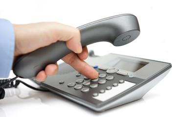 Businessman finger pressing a number button on the land line tel