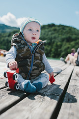 Adorable baby boy sitting outdoors on a wood deck