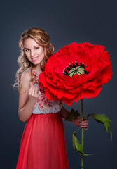 The curly blonde girl with a huge red poppy-flower in her hand
