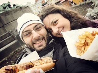 Young couple while taking a Selfie with street food.