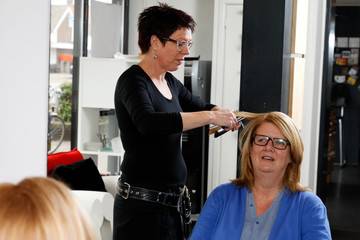 hairdresser and customer in front of a mirror in a salon