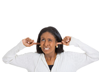 stressed woman covering her ears looking up stop making noise