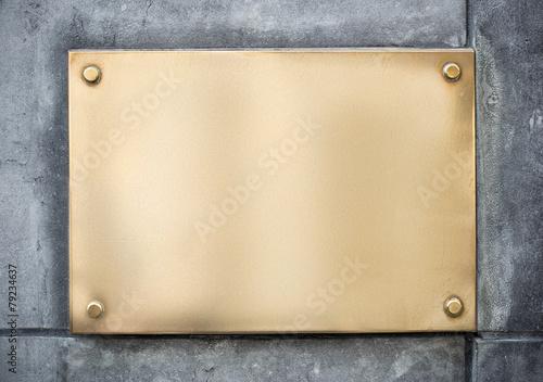 Leinwandbild Motiv blank gold or brass metal sign or nameboard on concrete wall