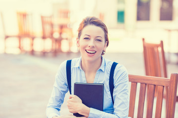 Laughing young woman with book outdoors on sunny day