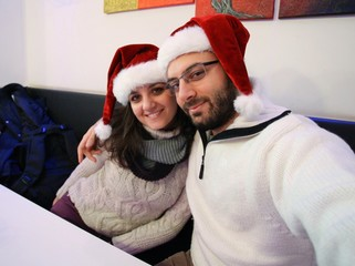 Young couple while taking a Selfie with santa claus hat.
