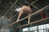 Athlete topless doing exercises on the uneven bars