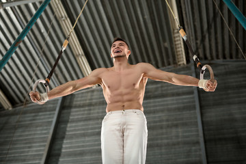 Athlete topless makes a difficult exercise on gymnastic rings in