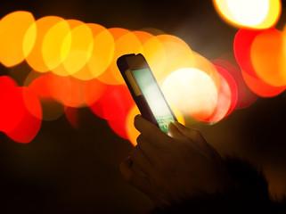 Woman hand smart phone glowing screen night light colorful bokeh