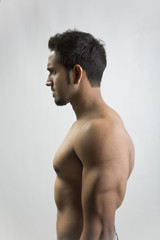 A young and fit male model posing his muscles