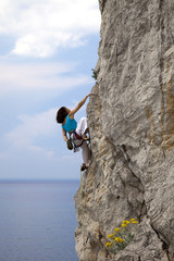 Female climber climbs wall in over the sea