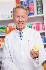 Smiling senior pharmacist holding medicine jar