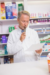 Serious senior pharmacist reading prescription