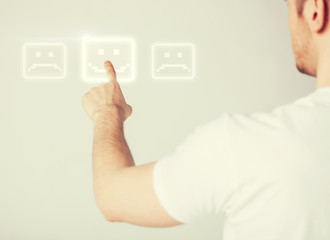 hand touching virtual screen with smile button