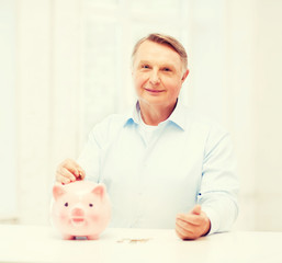 old man putting coin into big piggy bank