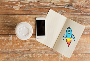 close up of notebook, coffee cup and smartphone