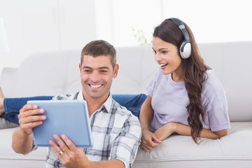 Man showing digital tablet to surprised woman