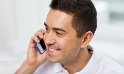 happy man calling on smartphone at home