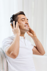 happy man in headphones listening to music at home