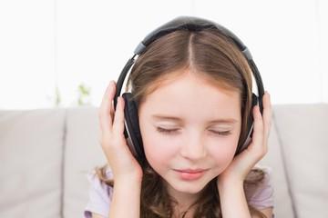 Girl with eyes closed listening music through headphones